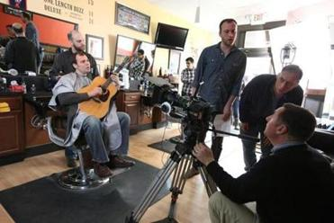 "Alastair Moock, with guitar, shoots his ""When I Get Bald"" music video at a Melrose barber shop."